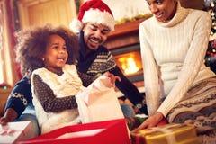 Lyckliga julklappar för Afro--amerikan familjöppning royaltyfri fotografi