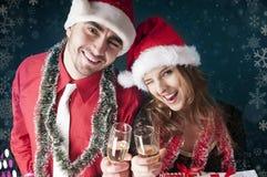 Lyckliga julpar med exponeringsglas av champagne Arkivbild