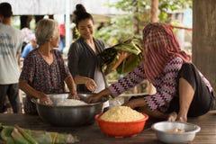 Lyckliga kakor för ris för danande för kvinna för asiatCambodja en khmer med bönor och banansidor Royaltyfri Fotografi