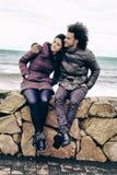 Lyckliga kalla par framme av havet i vintern Arkivbilder