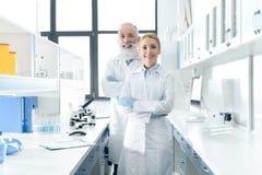 Lyckliga kemister i vita lag som står i kemiskt laboratorium med mikroskop och flaskor Fotografering för Bildbyråer