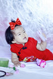Lyckliga kinesiska små behandla som ett barn i röd cheongsam har gyckel Royaltyfri Foto