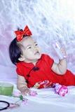 Lyckliga kinesiska små behandla som ett barn i röd cheongsam har gyckel Arkivfoto