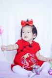 Lyckliga kinesiska små behandla som ett barn i röd cheongsam har gyckel Arkivfoton