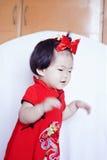 Lyckliga kinesiska små behandla som ett barn i röd cheongsam har gyckel Fotografering för Bildbyråer