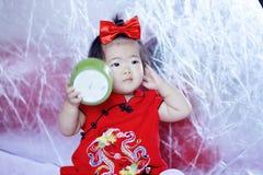 Lyckliga kinesiska små behandla som ett barn i röd cheongsam har gyckel Royaltyfri Bild