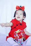 Lyckliga kinesiska små behandla som ett barn i röd cheongsam har gyckel Royaltyfri Fotografi