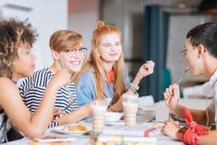 Lyckliga klasskompisar som talar, medan ha den deras matställen royaltyfria foton