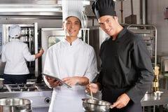 Lyckliga kockar som tillsammans lagar mat Arkivfoton