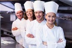 Lyckliga kockar team anseende tillsammans i kommersiellt kök Fotografering för Bildbyråer
