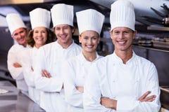 Lyckliga kockar team anseende tillsammans i kommersiellt kök Arkivbilder