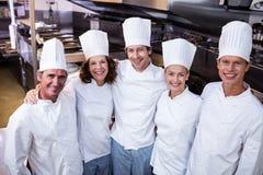 Lyckliga kockar team anseende tillsammans i kommersiellt kök Arkivfoto