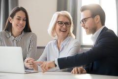 Lyckliga kollegor för affärslagfolk som talar skratta att arbeta tillsammans arkivbild