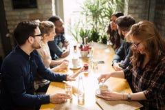Lyckliga kollegor från arbete som umgås i restaurang royaltyfria foton