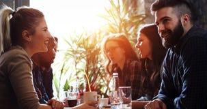Lyckliga kollegor från arbete som umgås i restaurang royaltyfri bild