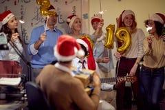 Lyckliga kollegor i jultomtenlock som har julgyckel royaltyfri bild