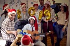 Lyckliga kollegor i jultomtenlock som har julgyckel- och lekgitarren arkivbilder