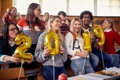 Lyckliga kollegor som har gyckel på beröm för nytt år på universitet royaltyfri fotografi