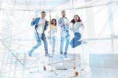Lyckliga kollegor som hoppar i luften arkivbilder