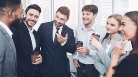Lyckliga kollegor som i regeringsställning talar och att ha kaffeavbrottet royaltyfri fotografi