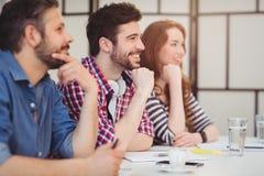 Lyckliga kollegor som sitter på skrivbordet i idérikt kontor arkivbilder