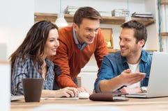 Lyckliga kollegor som tillsammans arbetar på bärbara datorn Royaltyfri Bild