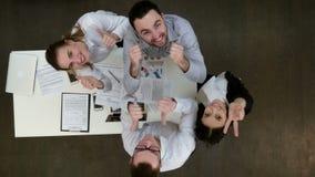Lyckliga kontorsarbetare som ler till kameran och visar upp tummar arkivfilmer