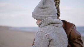 Lyckliga kramar och kyss av den härliga modern i utskrivaven hatt för vinter leopard och hennes litet barnson utomhus på havsstra stock video