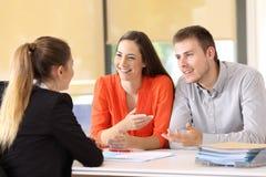 Lyckliga kunder som talar med kontorsarbetaren royaltyfria bilder