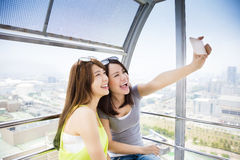 Lyckliga kvinnaflickvänner som tar en selfie i ferrishjul Royaltyfri Fotografi