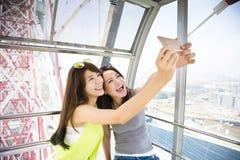 Lyckliga kvinnaflickvänner som tar en selfie i ferrishjul Royaltyfri Bild