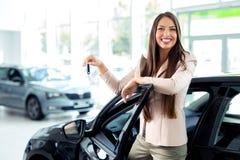 Lyckliga kvinnainnehavtangenter till hennes nya bil på återförsäljaren royaltyfria bilder