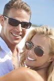 Lyckliga kvinnamanpar i solglasögon på stranden Fotografering för Bildbyråer