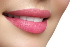 Lyckliga kvinnas för makro leende med sunda vita tänder, ljus rosa färg Royaltyfria Bilder