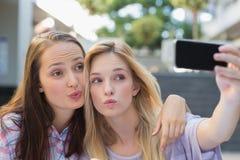 Lyckliga kvinnavänner som tar en selfie Royaltyfri Bild