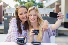 Lyckliga kvinnavänner som tar en selfie Arkivfoto