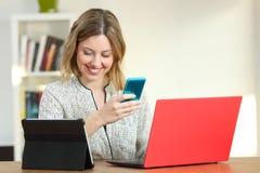Lyckliga kvinnliga användande åtskilliga färgrika apparater hemma fotografering för bildbyråer