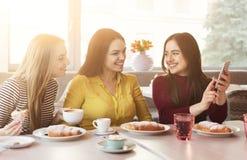 Lyckliga kvinnliga frinds med kaffe och smartphonen på kafét royaltyfria foton