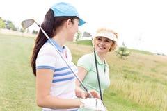 Lyckliga kvinnliga golfare som talar på golfbanan Arkivbilder