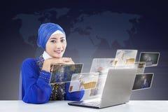 Lyckliga kvinnliga muslim som söker online-bilder på bärbara datorn Royaltyfri Bild