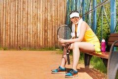 Lyckliga kvinnliga tennisspelaren som den har, vilar efter lek Arkivfoton