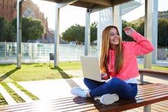 Lyckliga kvinnliga tonåringhälsninghälsningar, medan sitta med den öppna bärbara datorn utomhus arkivbilder