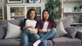 Lyckliga kvinnliga vänner håller ögonen på rolig film som skrattar, talar och äter tillsammans popcorn som hemma sitter på soffan arkivfilmer