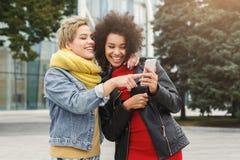 Lyckliga kvinnliga vänner lyssnar till musik utomhus royaltyfria bilder