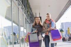 Lyckliga kvinnliga vänner med shoppingpåsar som går på trottoaren Arkivbild