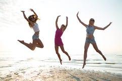 Lyckliga kvinnliga vänner som dansar och hoppar på stranden Arkivfoto