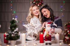 Lyckliga kvinnliga vänner som spelar i jul, dekorerade inre Fotografering för Bildbyråer