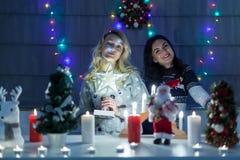 Lyckliga kvinnliga vänner som spelar i jul, dekorerade inre Royaltyfri Bild