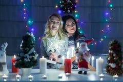 Lyckliga kvinnliga vänner som spelar i jul, dekorerade inre Royaltyfri Fotografi