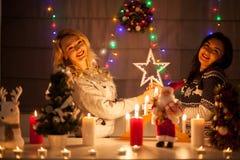 Lyckliga kvinnliga vänner som spelar i jul, dekorerade inre Arkivfoto